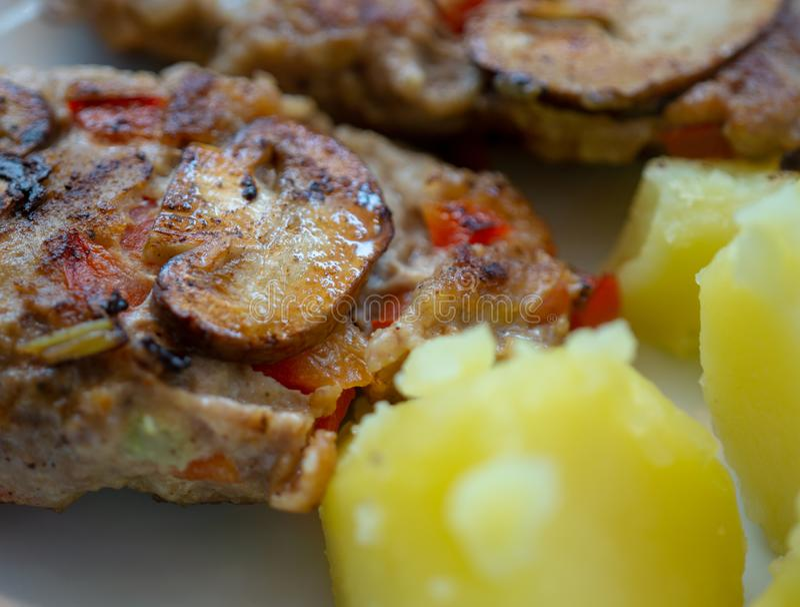 De kruidige gebraden paddestoelen op geroosterd vegetrarischen vleesballetje met gekookte aardappels als bijgerecht, het gezonde  stock fotografie