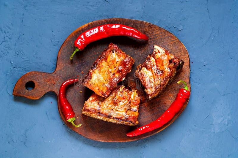 De kruidige hete geroosterde krabbetjes van BBQ dienden met hete Spaanse peperpeper op houten raad op blauwe achtergrond van beto stock foto