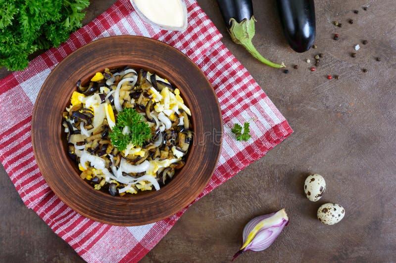 De kruidige salade van gebraden aubergine, gekookt ei, marineerde uien in een kom stock fotografie