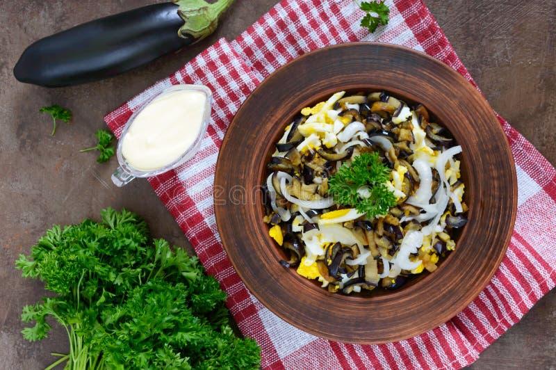 De kruidige salade van gebraden aubergine, gekookt ei, marineerde uien in een kom royalty-vrije stock afbeeldingen