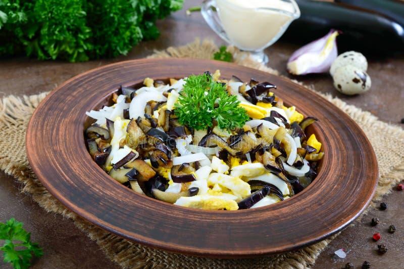 De kruidige salade van gebraden aubergine, gekookt ei, marineerde uien in een kom stock foto