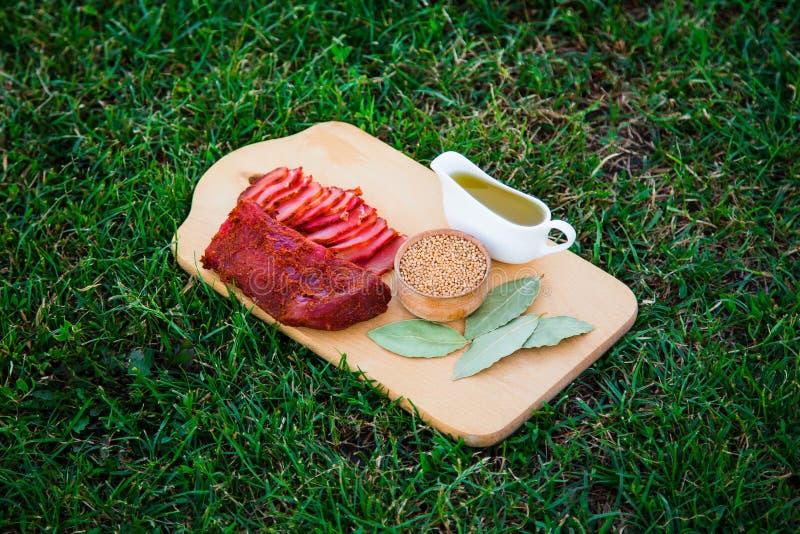 De kruidige stukken van vlees worden voorgesteld met kruiden op een houten raad stock fotografie