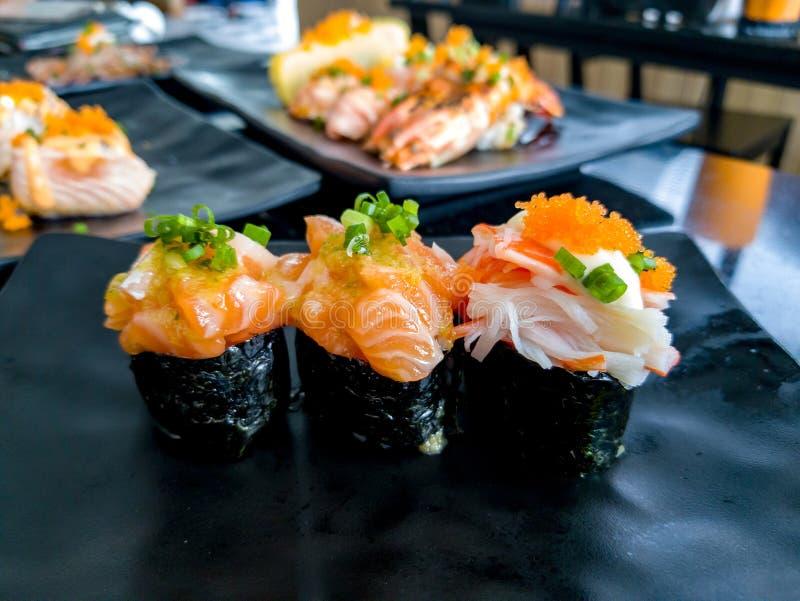 De kruidige sushi van de Zalmsalade en de sushi van Mayo Kani zetten op een zwarte plaat in Japans restaurant stock foto