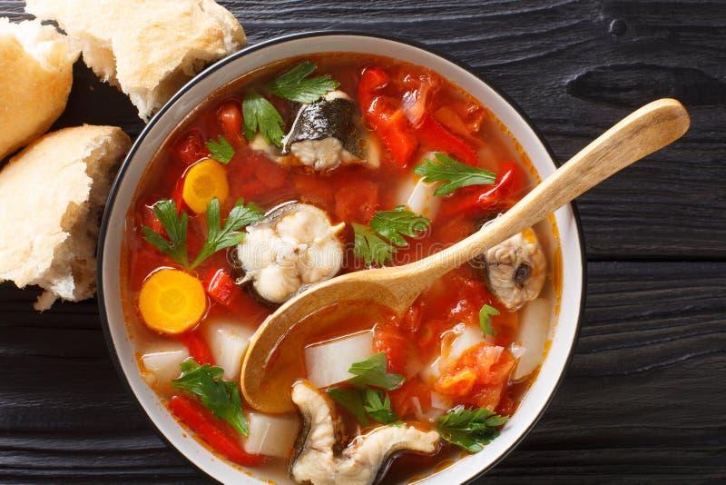 De kruidige vissensoep met paling, tomaten en ander groentenclose-up in een kom diende met brood horizontale hoogste mening stock foto's