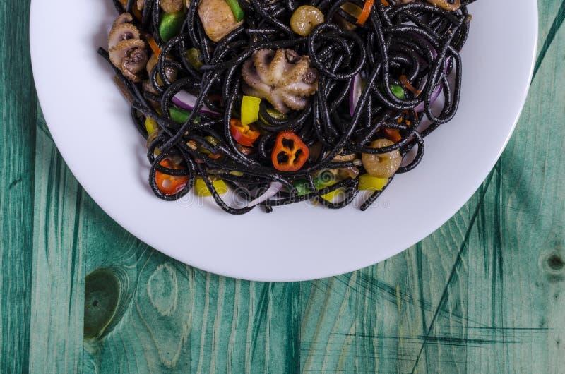 De kruidige zwarte spaghettischotel met zeevruchten en de groenten op een wit plateren groene houten hoogste mening als achtergro stock foto's