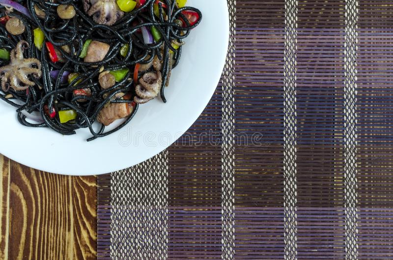 De kruidige zwarte spaghettischotel met zeevruchten en de groenten op een wit plateren veelkleurige hoogste mening als achtergron royalty-vrije stock afbeeldingen