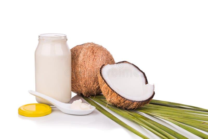 De kruik die kokosnotenolie bevatten wordt gebruikt zoals kokend ingrediënt royalty-vrije stock foto's