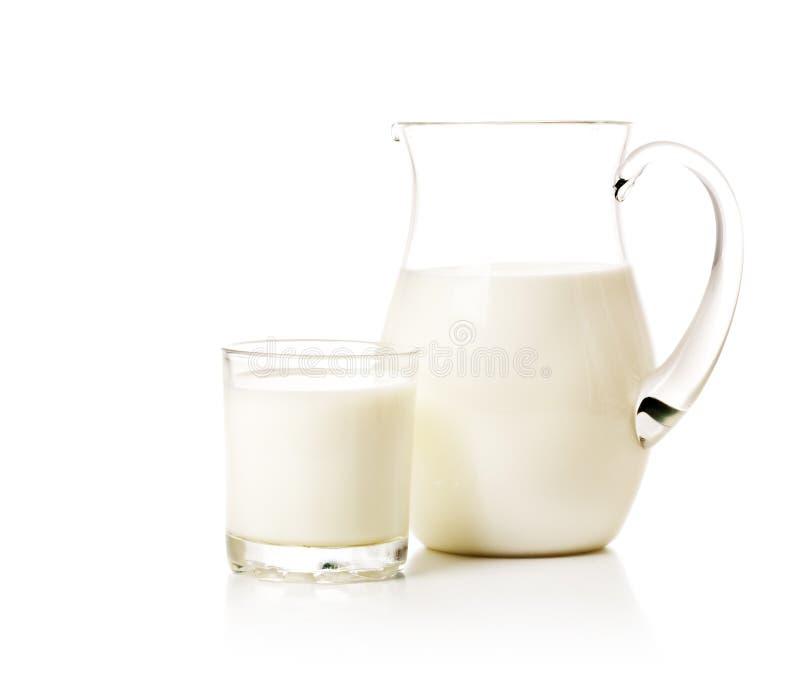 De kruik en het glas van de melk stock foto's