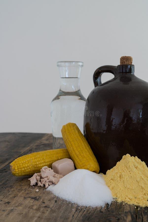 De kruik en de ingrediënten van maneschijndemi op rustieke houten lijst stock afbeeldingen