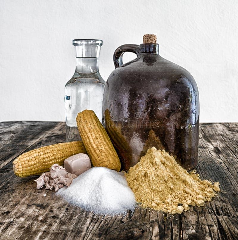 De kruik en de ingrediënten van maneschijndemi op rustieke houten lijst royalty-vrije stock foto