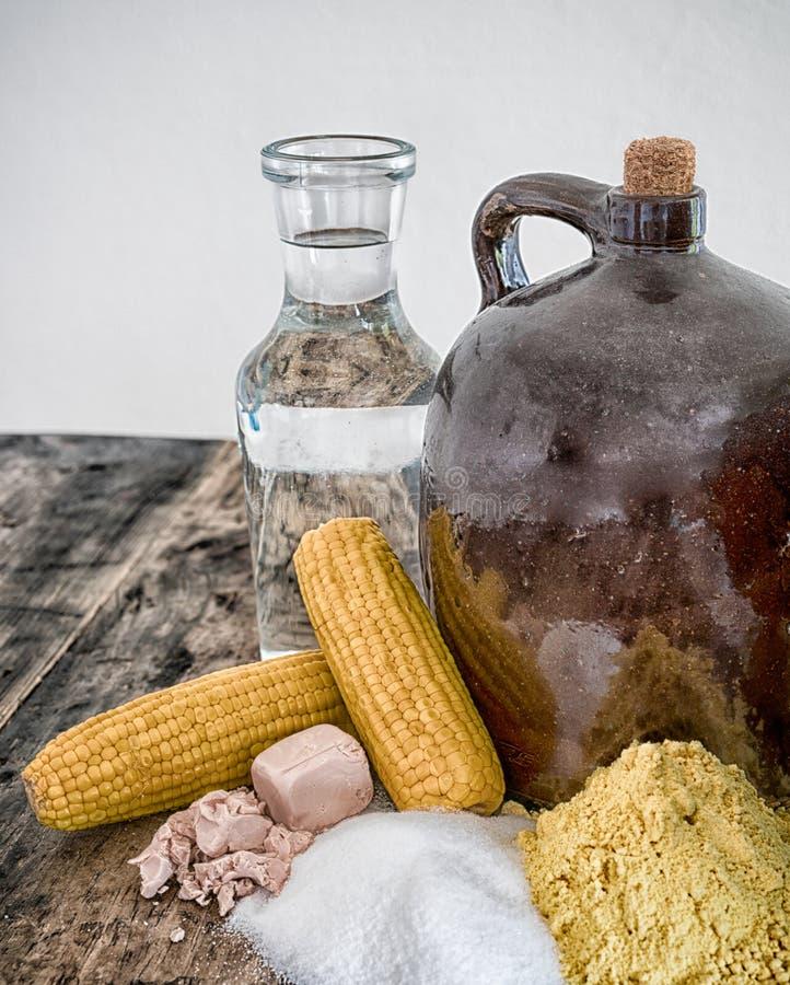 De kruik en de ingrediënten van maneschijndemi op rustieke houten lijst stock afbeelding