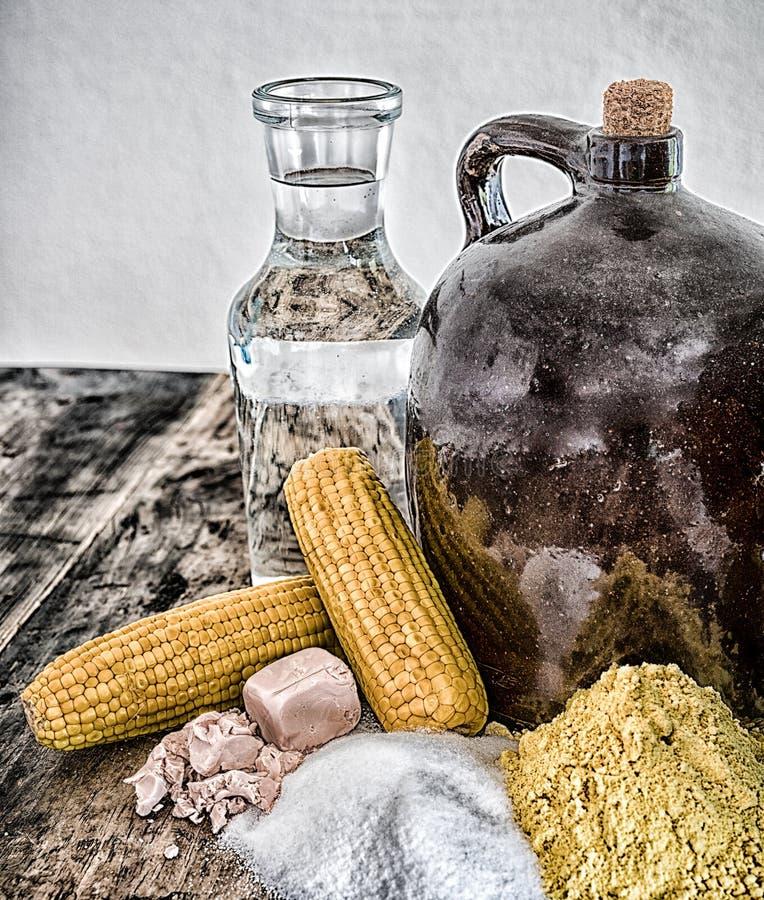 De kruik en de ingrediënten van maneschijndemi op rustieke houten lijst royalty-vrije stock afbeeldingen