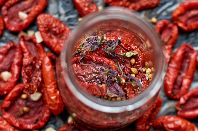 De kruik met vele droge rode tomaten, de olijf en de kruiden op een donkere oppervlakte sluiten omhoog Droge tomatentextuur vage  stock fotografie