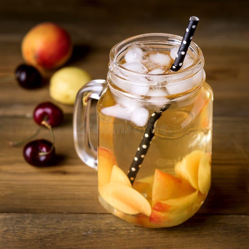 De kruik de Thee van het Perzikijs met Verse Vruchten op de Rustieke Houten Smakelijke Verse Zomer Als achtergrond drinkt Vierkan royalty-vrije stock fotografie