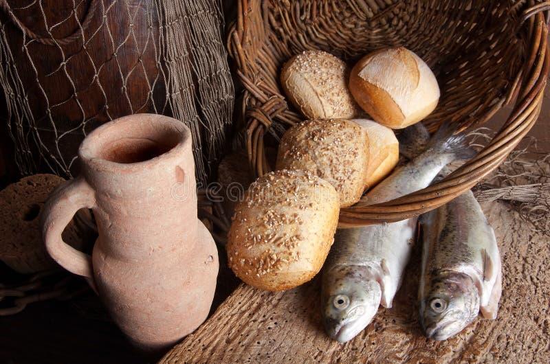 De kruik van de wijn met brood en vissen stock foto's