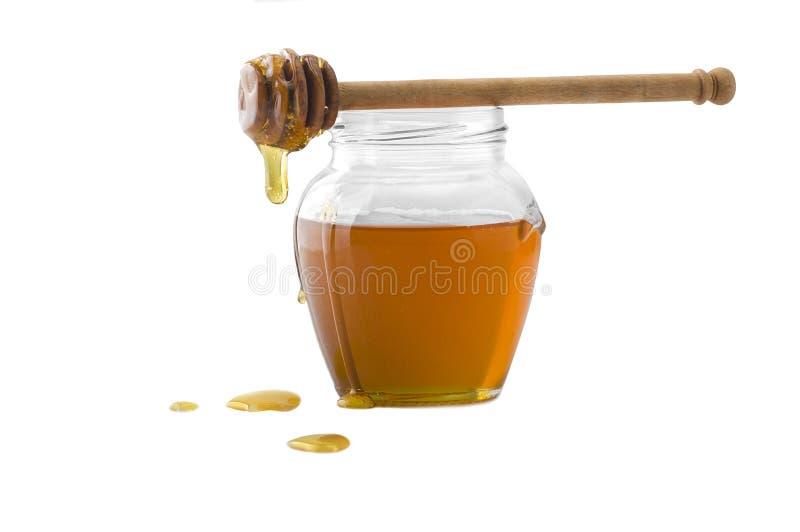 De kruik van het glas honing stock foto