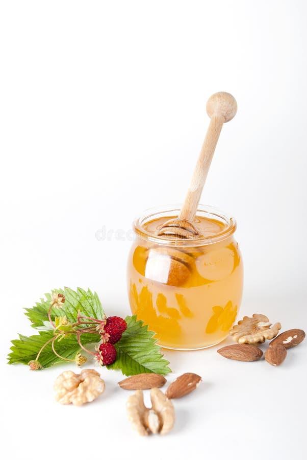 De Kruik van het glas honing met houten drizzler royalty-vrije stock foto
