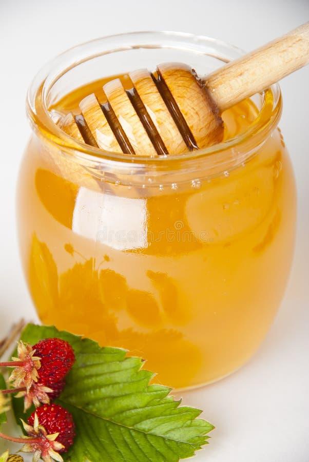 De Kruik van het glas honing met houten drizzler stock foto's