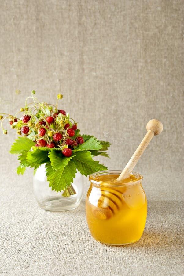 De Kruik van het glas honing met houten drizzler royalty-vrije stock afbeeldingen