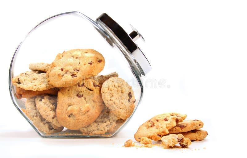 De kruik van het glas met koekjes tegen een wit stock fotografie