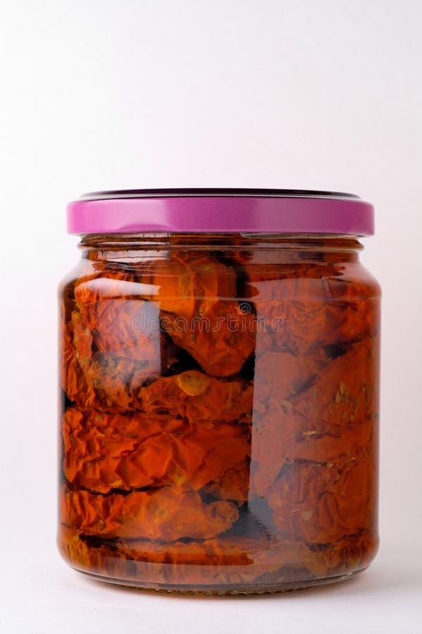 De kruik van het glas van bewaarde tomaten stock afbeelding