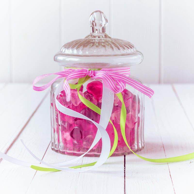 De kruik van het glassuikergoed met roze kleverig suikergoed wordt gevuld dat royalty-vrije stock foto's