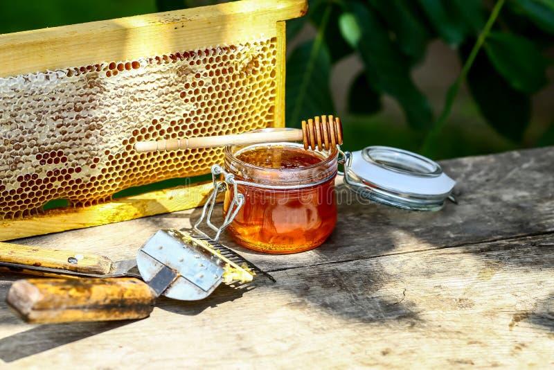 De kruik verse honing met geassorteerde hulpmiddelen voor imkerij, een houten automaat en een dienblad van honingraat van een bij royalty-vrije stock fotografie
