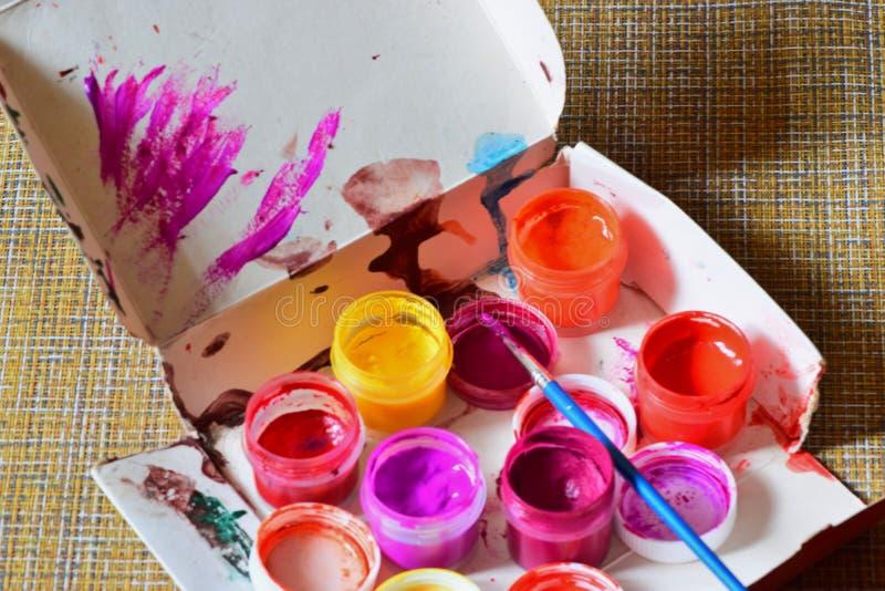 De kruiken met kleurrijke heldere kleuren en een borstel worden voorbereid op het kunstenaars` s werk royalty-vrije stock foto's