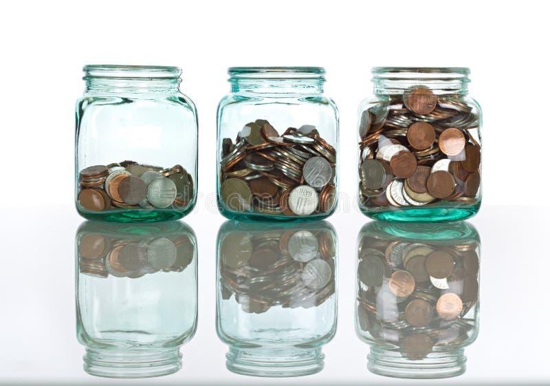De kruiken van het glas met muntstukken - besparingenconcept stock foto