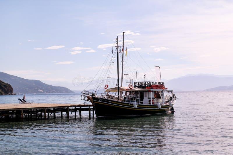 De kruiser van de toeristenboot in kleine jachthaven op overzees en mooi strand, wachtende toeristen voor schip vaart uit haven v stock foto