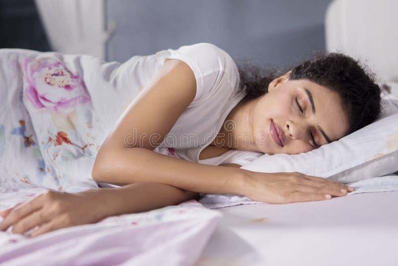 De krullende haarvrouw rust in bed stock fotografie