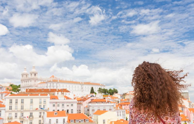 De krullende jonge vrouw met wind in haar haar bekijkt mooie Li royalty-vrije stock afbeelding