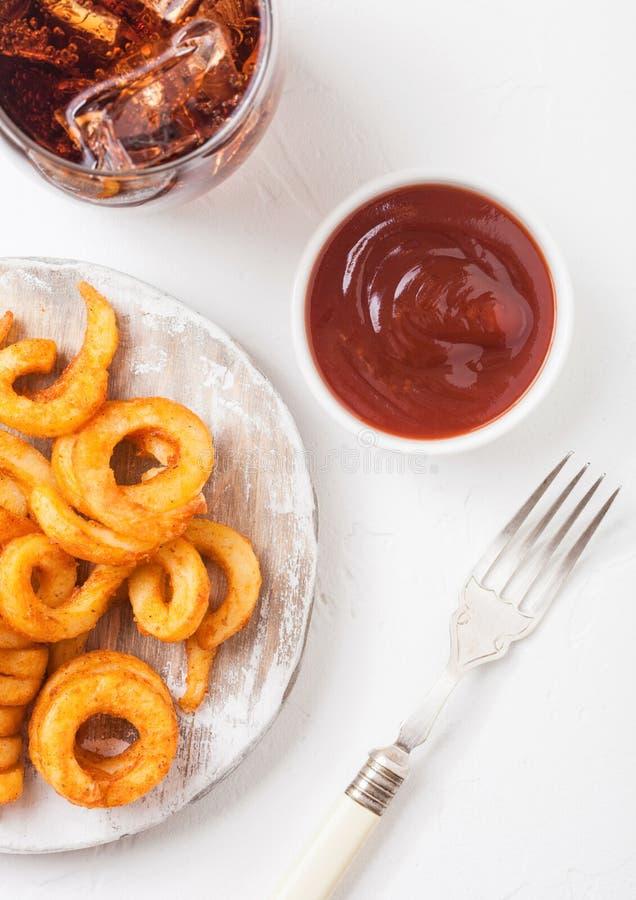 De krullende snack van het gebraden gerechten snelle voedsel op houten raad met ketchup en glas kola op de achtergrond van de ste stock foto