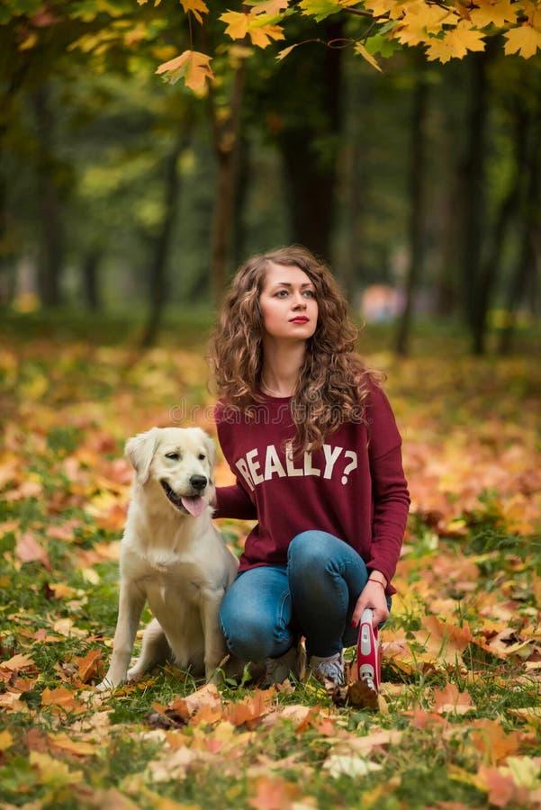 De krullende vrouwenzitting met haar hond in de herfst gaat in openlucht weg stock afbeeldingen