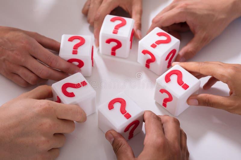 De Kubieke Blokken van de zakenluiholding met Vraag Mark Sign stock fotografie