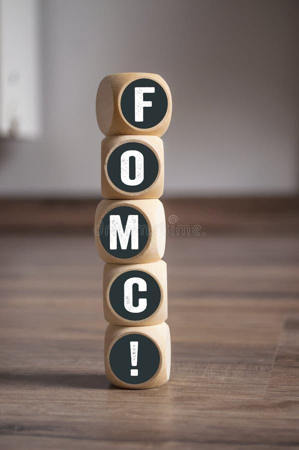 De kubussen dobbelen met Federaal de Open Marktcomité van FOMC voor houten achtergrond royalty-vrije stock afbeeldingen