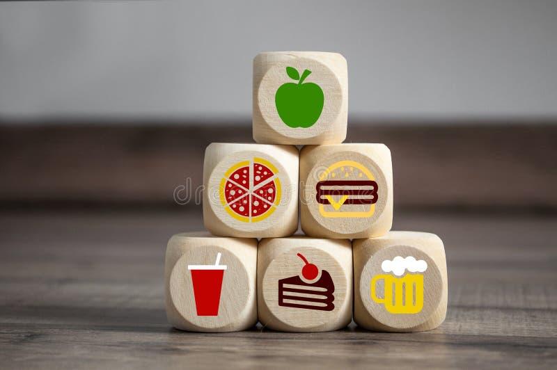 De kubussen en dobbelen met snel voedsel smybols en op bovenkant een appel voor dieet stock foto