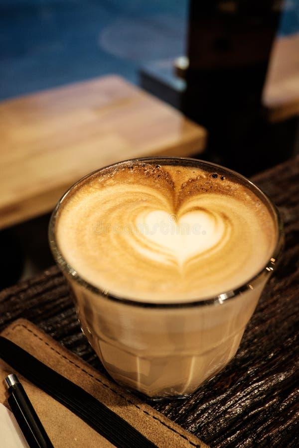 De kunst hete koffie van de hartvorm latte met het notitieboekje van de leerdekking royalty-vrije stock afbeelding