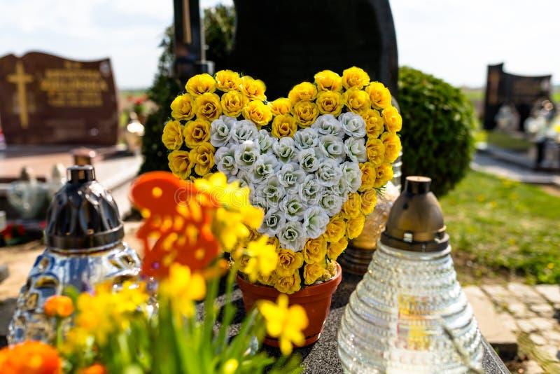 De kunstbloemen in de vorm van een hart en de kandelaars liggen op de grafsteen in de begraafplaats stock foto's