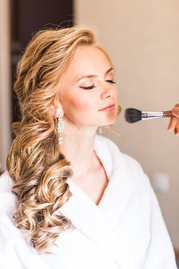 De kunstenaar die van de huwelijksmake-up bruid maken goedmaken Mooi sexy modelmeisje binnen De vrouw van het schoonheidsblonde m stock foto
