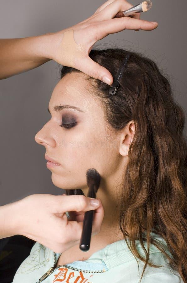 De kunstenaar die van de make-up basisstichting toepast om te modelleren stock afbeelding