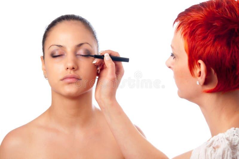 De kunstenaar die van de make-up make-up op wenkbrauw toepast stock afbeeldingen