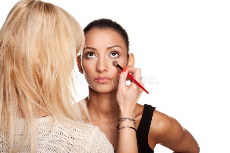 De kunstenaar die van de make-up make-up toepast op haar model stock afbeelding