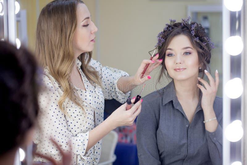 De kunstenaar die van de stilistmake-up make-up en haar in een schoonheidssalon doen Professionele Samenstelling royalty-vrije stock afbeelding