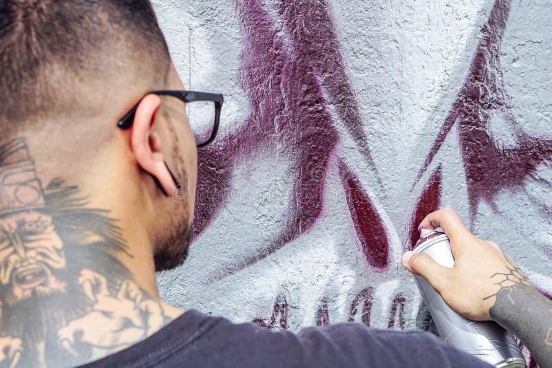 De kunstenaar die van de straatgraffiti met een kleurenaërosol een donkere graffiti van de monsterschedel op de muur in de stad s royalty-vrije stock afbeelding