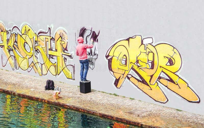 De kunstenaar die van de straatgraffiti met een kleurenaërosol een graffiti op de muur in de stad schilderen - Concept eigentijds royalty-vrije stock foto's