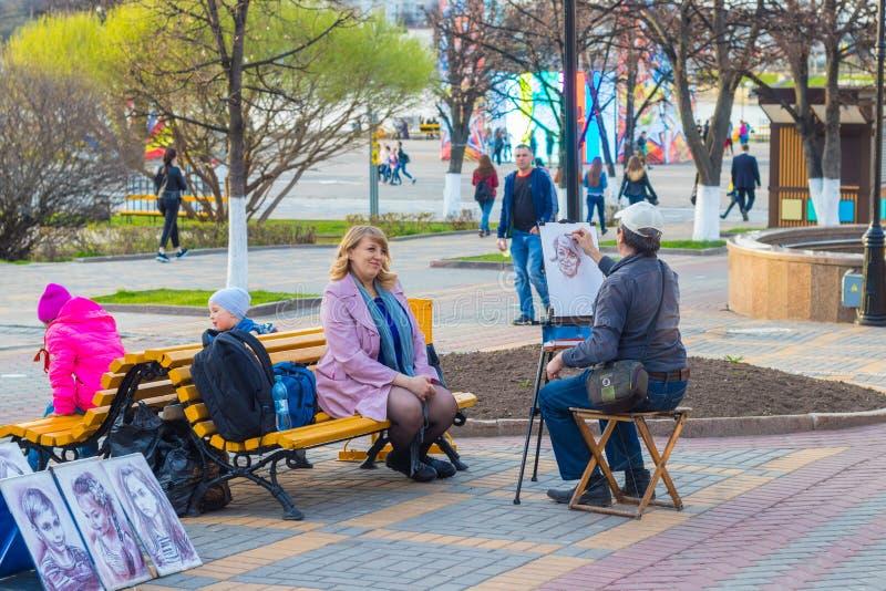 De kunstenaar in het park schildert een portret van een vrouw Cheboksary, Rusland, 07/05/2018 royalty-vrije stock foto's