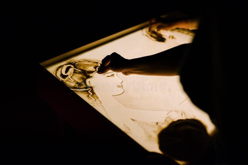De kunstenaar trekt zand Animatie op het zand stock afbeeldingen