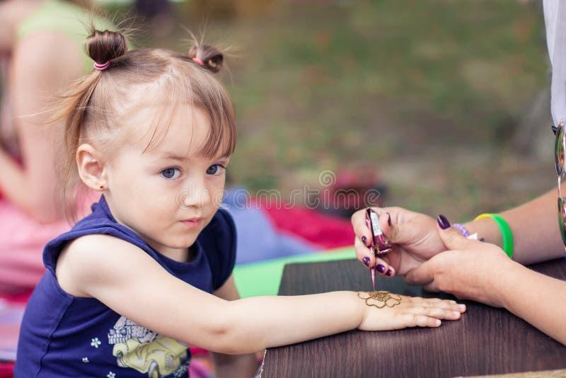 De kunstenaar van vrouwenmehendi het schilderen henna op de kind` s hand stock foto