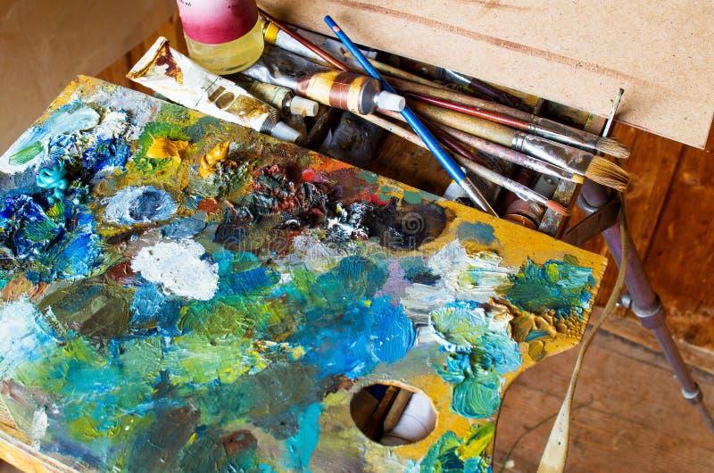 De kunstenaars` s hulpmiddelen: borstels, palet, verven, schildersezel stock afbeeldingen